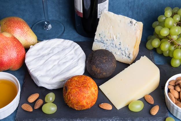 Cheese plate. 5 species of cheese, fruit, nuts, bottle of wine. close-up, selective focus.