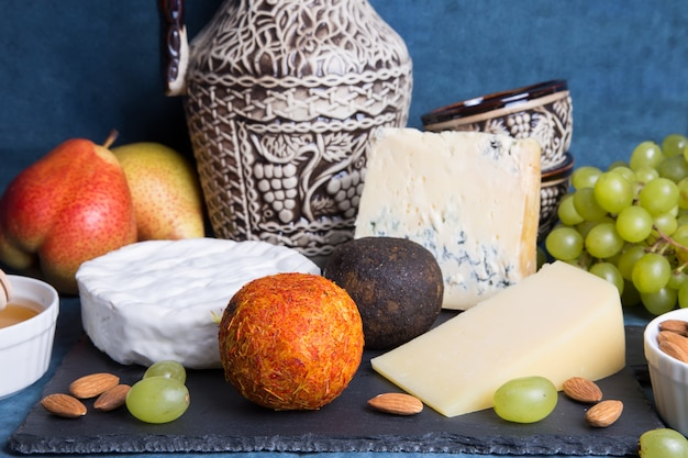 Cheese plate. 5 species of cheese, fruit, nuts, wine jug. close-up, selective focus.