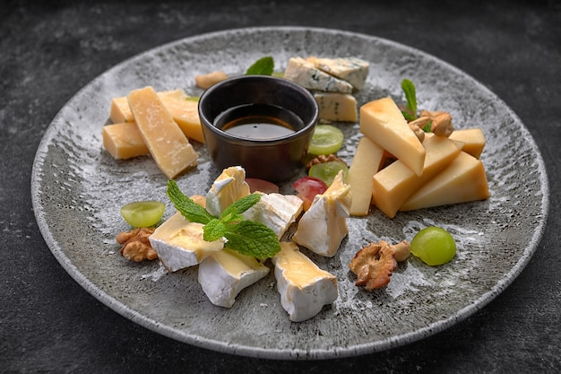 Cheese plate, assorted cheeses with mint, candied fruit, honey and cookies, on a plate