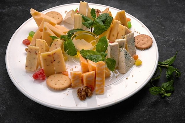 Cheese plate, assorted cheeses with mint, candied fruit, honey and cookies, on a white plate, on a dark background