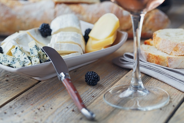 チーズプレート。木製の背景にベリーとロゼワインのグラスとチーズの品揃え。
