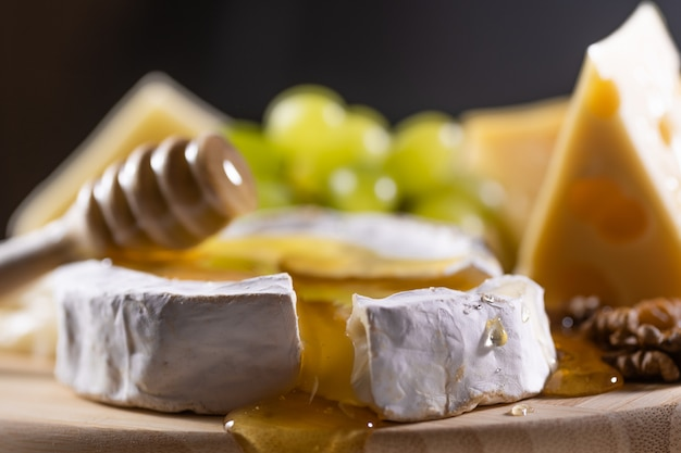 Cheese plate, honey pouring on camembert cheese