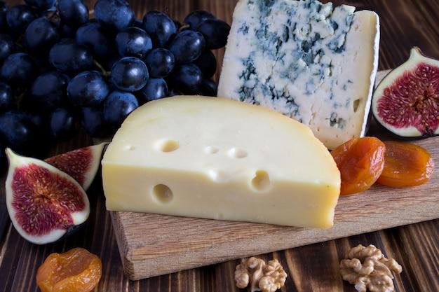 茶色の木製の背景にチーズプレート