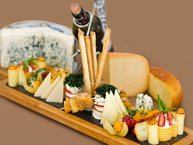 Cheese plate: roquefort with blue mold, cheddar, smoked cheese, mozzarella on a wooden board.