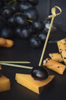 チーズプレートは、暗い背景にクラッカー、ブドウ、白ワインのグラスを添えて。テイスティングプレート上の古いゴーダチーズ。閉じる