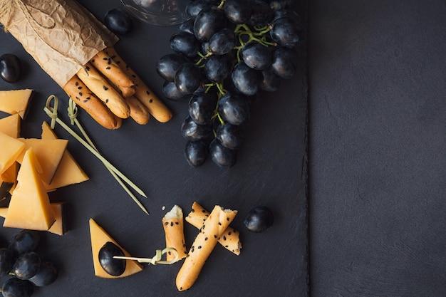 チーズプレートは、暗い背景にクラッカー、ブドウ、白ワインのグラスを添えて。テイスティングプレート上の古いゴーダチーズ。コピースペースのある上面図。