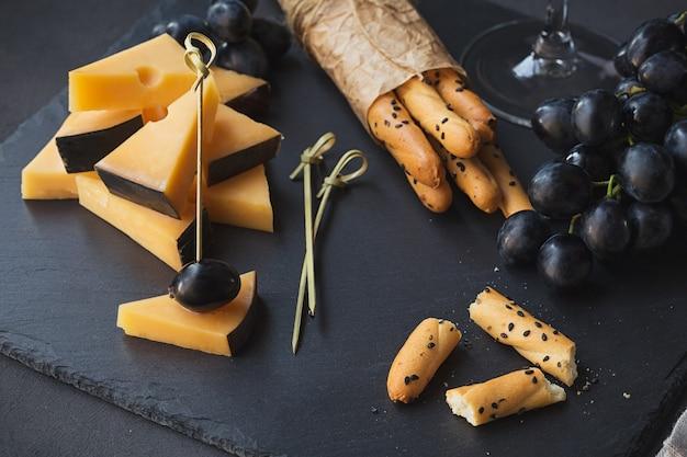 チーズプレートは、暗い背景にクラッカー、ブドウ、白ワインのグラスを添えて。テイスティングプレート上の古いゴーダチーズ