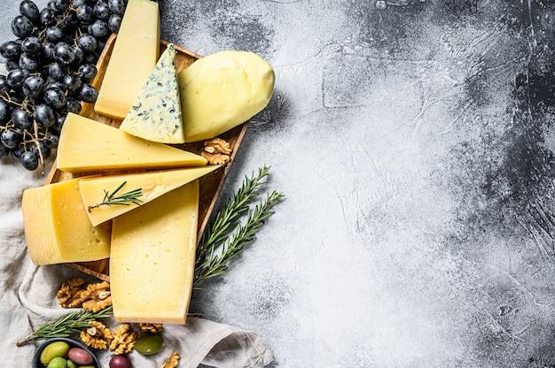 치즈 플레이트는 포도, 크래커, 올리브 및 견과류와 함께 제공됩니다. 맛있는 간식 모듬. 회색 배경. 평면도. 텍스트를위한 공간