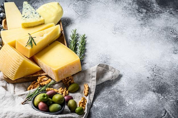 チーズプレートには、ブドウ、クラッカー、オリーブ、ナッツが添えられています。おいしいスナック盛り合わせ。上面図。 copyspaceの背景