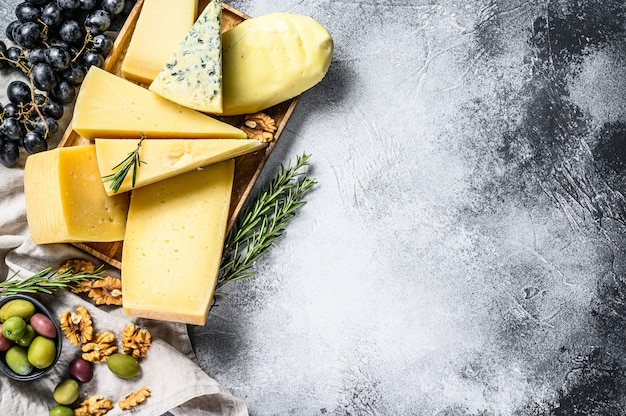 Cheese plate served with grapes, crackers, olives and nuts. assorted delicious snacks. gray background. top view. space for text