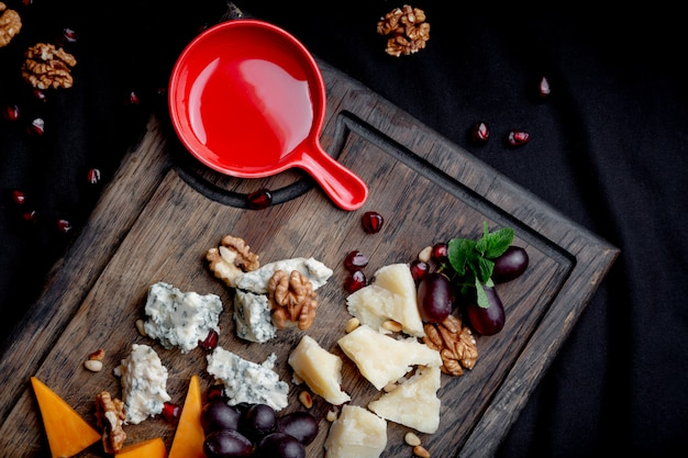 Cheese plate served with grapes, honey and nuts