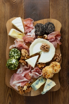 Cheese plate, various types of cheeses, grapes, walnuts and honey and prosciutto.