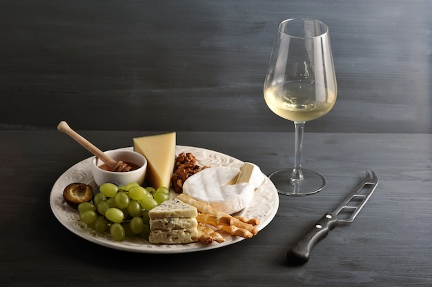 Cheese plate, wine and cheese knife on dark