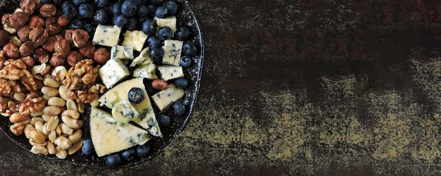 Cheese plate with blue cheese, nuts and blueberries. healthy snack. keto diet