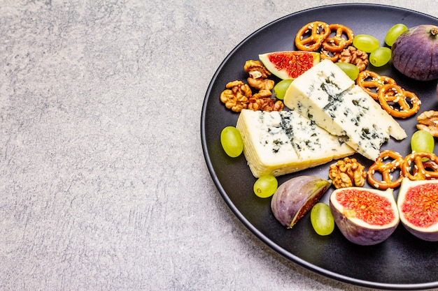 Cheese plate with blue cheese, walnuts, figs, grapes, pretzels