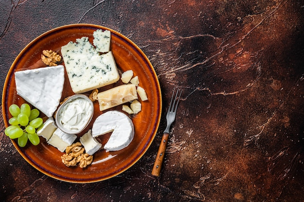 브리, 카망베르, 로크 포르, 블루 크림 치즈, 포도, 견과류가 들어간 치즈 플레이트. 어두운 배경. 평면도. 공간을 복사하십시오.
