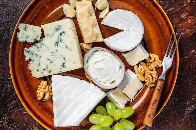 브리, 카망베르, 로크 포르, 블루 크림 치즈, 포도, 견과류가 들어간 치즈 플레이트. 어두운 배경. 평면도.