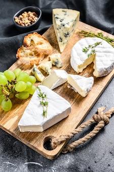Сырная тарелка с камамбером, бри и голубым сыром с виноградом и грецкими орехами. черный фон. вид сверху