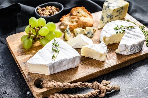 カマンベールチーズ、ブリーチーズ、ブルーチーズとブドウとクルミのチーズプレート。黒の背景。上面図。