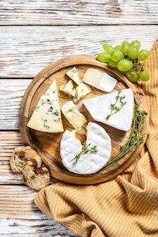 Сырная тарелка с камамбером, бри и голубым сыром с виноградом. белый деревянный фон. вид сверху