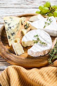 Сырная тарелка с камамбером, бри и голубым сыром с виноградом. ,