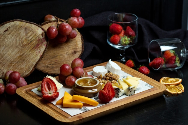 Cheese plate with cheddar, white and gouda cheese, strawberry, honey, walnut and grape