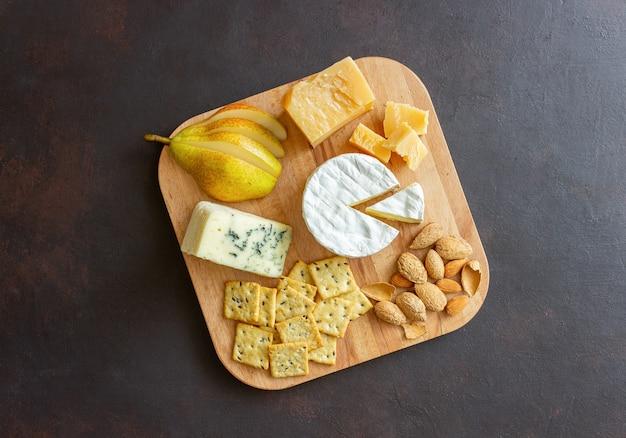 Сырная тарелка с крекером, миндалем и виноградом. винная закуска. закуска к вину.