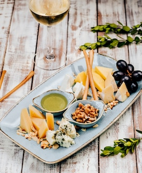 Cheese plate with crispy sticks and grapes