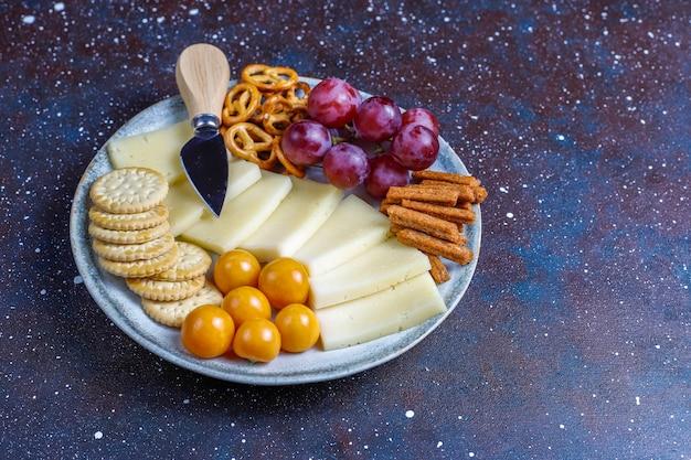 Сырная тарелка с восхитительным сыром тильзитер и закусками.