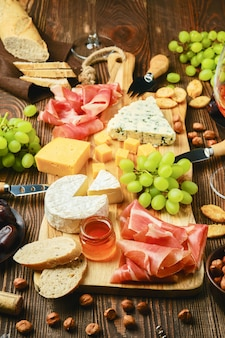 ドルブル、ブリー、チェダー、生ハム、ブドウ、蜂蜜、ナツメヤシシロップ、クラッカー、ナッツ、ワインのチーズプレート