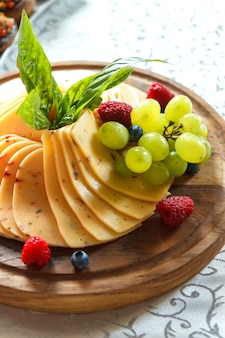 Cheese plate with fruit on the table