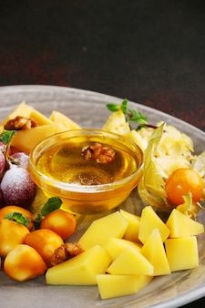 ブドウ、ホオズキ、蜂蜜、ナッツの入ったチーズ プレートの接写。
