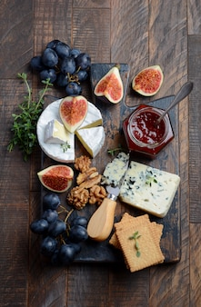 Cheese plate with grapes, figs, crackers, honey, plum jelly, thyme and nuts.