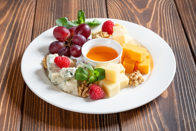 Cheese plate with grapes, honey and berries