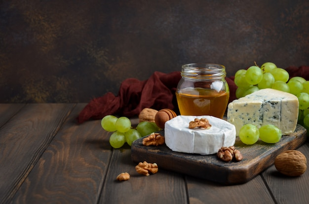 Cheese plate with grapes, honey and nuts on dark background.