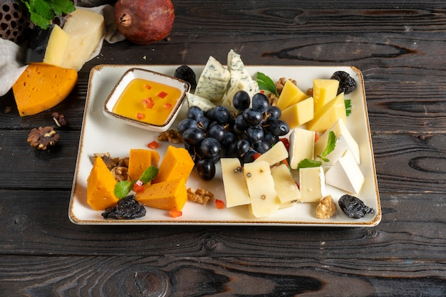 Cheese plate with grapes, honey, prunes and walnuts.