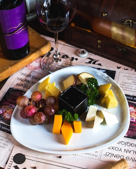 Cheese plate with grapes served with wine