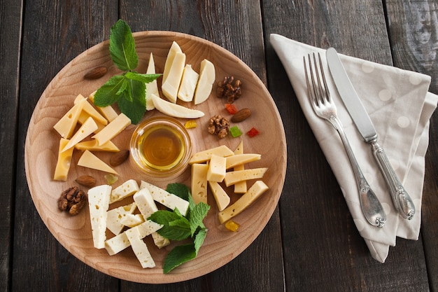 Cheese plate with honey and cutlery on wooden