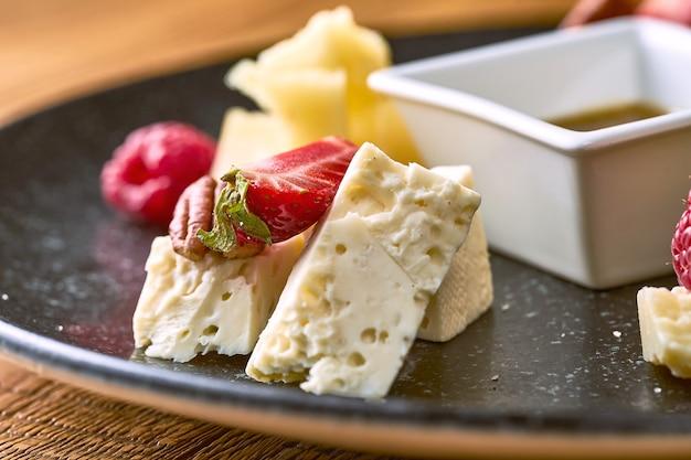 Сырная тарелка с медом, орехами и клубникой. вид на камамбер крупным планом
