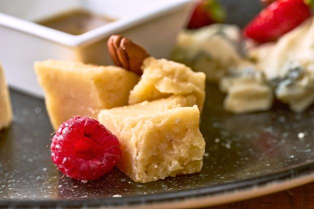 Сырная тарелка с медом, орехами и клубникой. крупным планом вид на твердый сыр