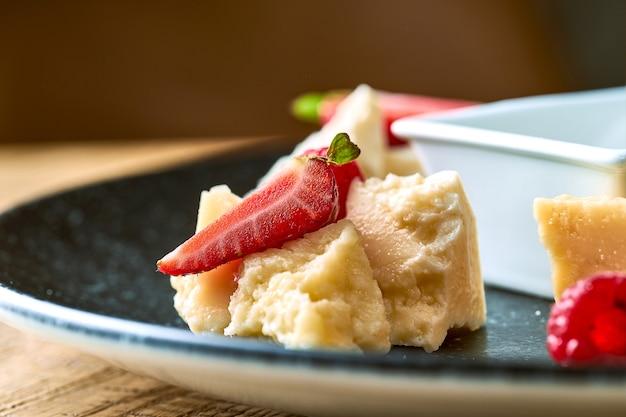 Сырная тарелка с медом, орехами и клубникой. крупным планом вид на сыр пармезан