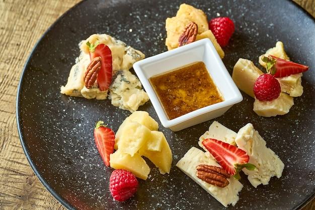 Сырная тарелка с медом, орехами и клубникой. деревянный фон
