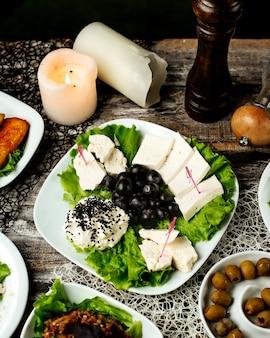 Piatto di formaggi con lattuga e olive