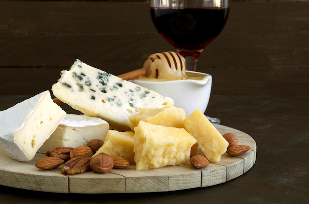 Cheese plate with nuts and honey on dark background.