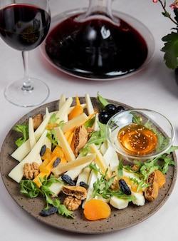 Cheese plate with nuts raisins arugula olives and glass of wine