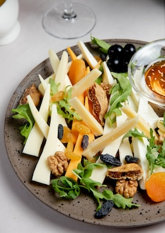 Cheese plate with nuts raisins arugula and olives