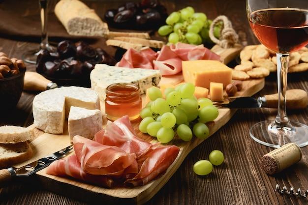 生ハム、ブドウ、蜂蜜、ナツメヤシ、クラッカー、ワインが入ったチーズプレート(前景に焦点を当てる)