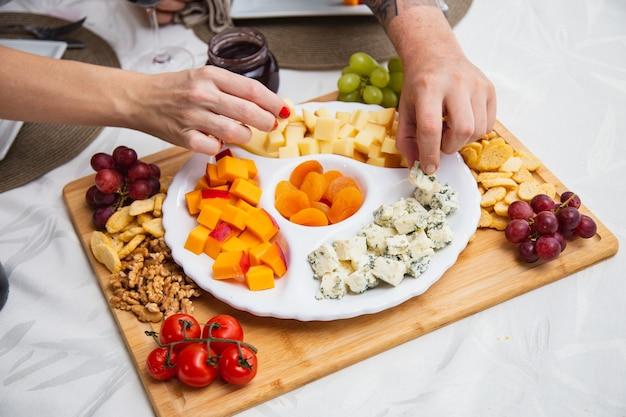 テーブルの上にさまざまな前菜が入ったチーズプレート。テーブルの上のイチゴ、アプリコット、ブドウ、穀物のチーズ料理