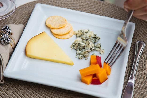 Сырная тарелка с множеством закусок на столе.