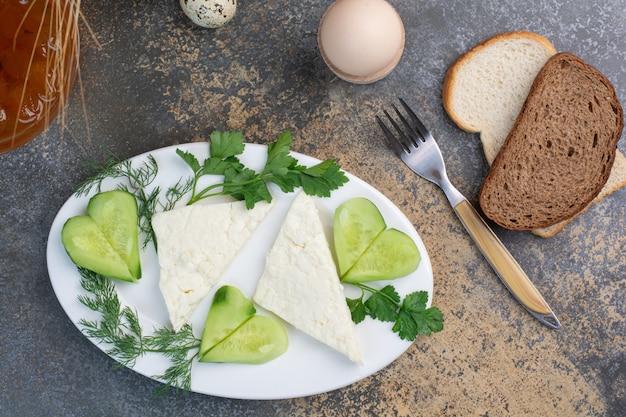 Piatto di formaggi con verdure e fette di pane.